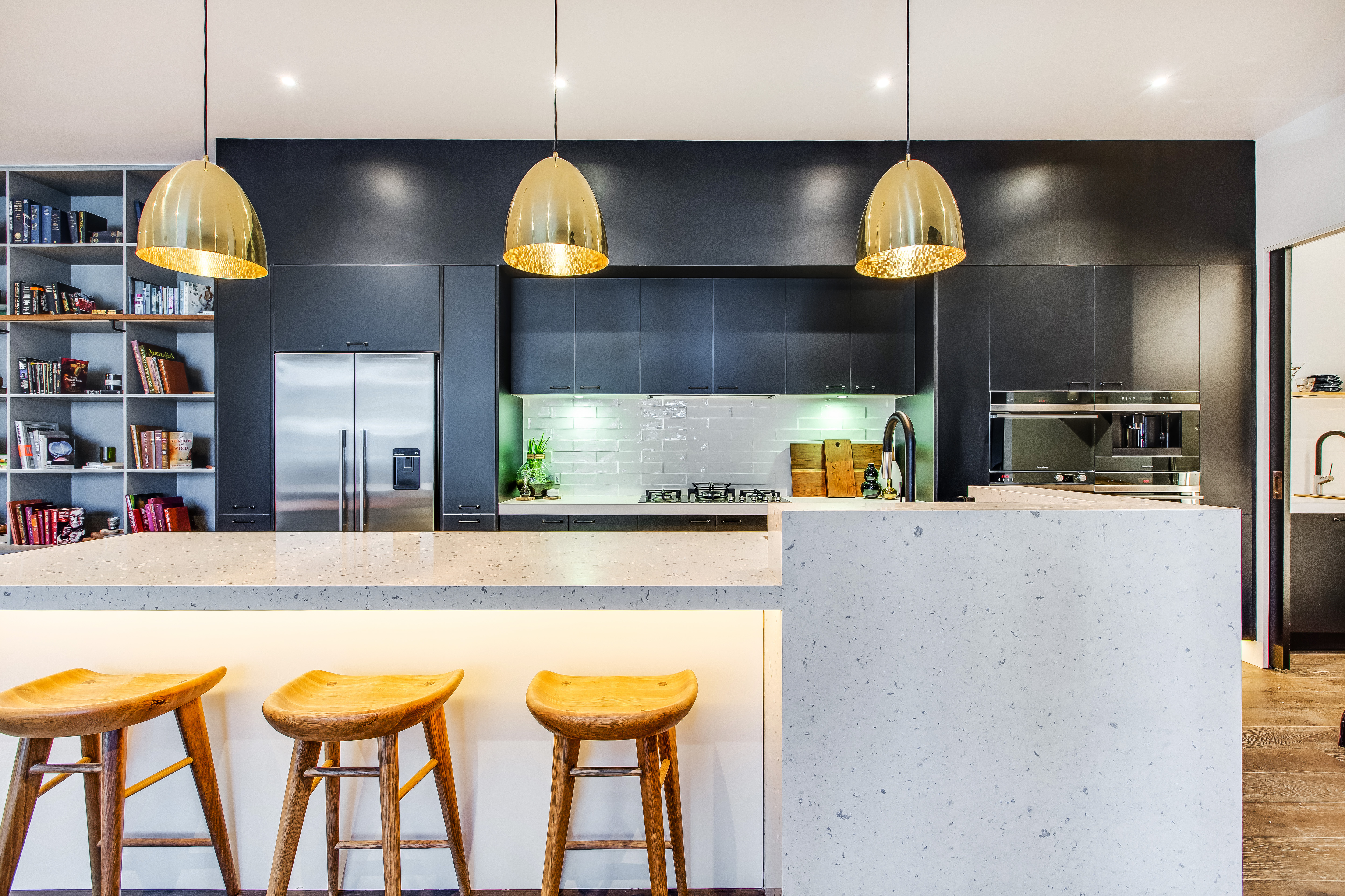 Block Glasshouse kitchen with laminate cabinetry, engineered stone bench, and engineered timber floorboards.